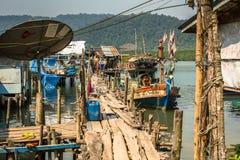 Hutten en vissersboot bij de pijler binnen bij vissersdorp Stock Afbeeldingen