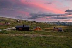 Hutten in landschap van Noorwegen tijdens zonsondergang stock foto