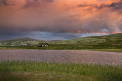 Hutten met meer in landschap van Noorwegen tijdens zonsondergang royalty-vrije stock foto's