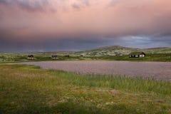 Hutten met meer in landschap van Noorwegen tijdens zonsondergang royalty-vrije stock afbeeldingen