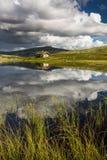 Hutten op meer in landschap van Noorwegen stock afbeelding