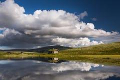 Hutten op meer in landschap van Noorwegen royalty-vrije stock afbeelding