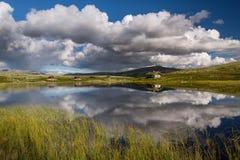 Hutten op meer in landschap van Noorwegen stock foto
