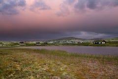 Hutten op meer in landschap van Noorwegen tijdens zonsondergang royalty-vrije stock afbeeldingen