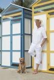 Huttes colorées de plage et homme supérieur avec le chien Image libre de droits
