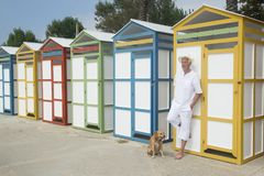 Huttes colorées de plage et homme supérieur avec le chien Photographie stock
