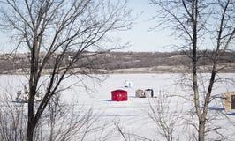 Huttes de pêche se reposant sur un lac congelé neigeux dans l'horaire d'hiver Image stock