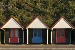 Huttes de plage avec les portes rouges et bleues avec des buissons à l'arrière-plan photographie stock