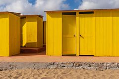 Huttes peintes jaune-foncé de plage, le jour ensoleillé mais déprimé Ciel bleu, nuages blancs, architecture de vacances de bord d images stock