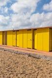 Huttes peintes jaune-foncé de plage, le jour ensoleillé mais déprimé Ciel bleu, nuages blancs, architecture de vacances de bord d photographie stock