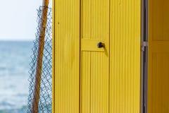 Huttes peintes jaune-foncé de plage, le jour ensoleillé mais déprimé Ciel bleu, nuages blancs, architecture de vacances de bord d photographie stock libre de droits