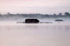 Huttes sur un lac brumeux photographie stock