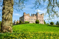 Hutton in the Forest, Cumbria, England. Green lawn in front of Hutton in the Forest castle in Cumbria, England on sunny day with blue skies Stock Images