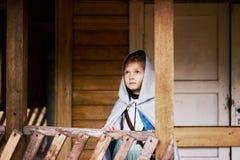 Huv för liten flickasilverkappa som ser för husbyggnad för himmel gammalt övergett rida för blåa ögon för berättelse för saga arkivfoton