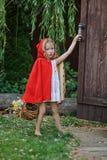 Huv för ridning för gulliga barnflickalekar liten röd i sommarträdgård Royaltyfria Foton