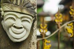 Huvud av en stenstaty för hinduisk gud av en person med ett leende på bakgrunden av ett staket royaltyfri foto