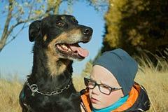 Huvud av hunden och pojken Arkivbild