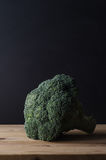 Huvud av mörker - grön broccoli på den Wood plankatabellen mot svarta lodisar Arkivbilder