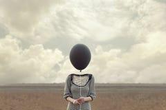 Huvud för kvinna` som s byts ut av en svart ballong arkivbild