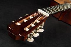 Huvud och fretboard av gitarren som ligger på tyg arkivbilder