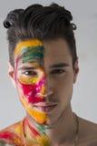 Huvud-skjutit av attraktiv ung man, färgar hud som målas med Holi arkivbilder