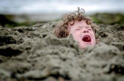 Huvud som klibbas i sanden, ibland en idiom arkivfoton