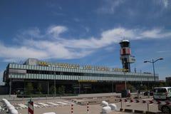 Huvudbyggnad för ankomster och avvikelse av den Rotterdam Haag flygplatsen i Nederländerna med trafiktornet arkivfoto
