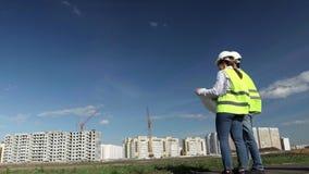Huvudbyggnadteknikererna är en man och en kvinna i gröna västar lager videofilmer