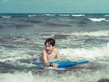 Huvuddel som surfar på stranden Arkivfoton