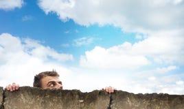 Huvudet av en man ser upp himlen, ser ut bakifrån ett konkret staket, fritt utrymme för designen, orientering Royaltyfria Foton