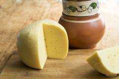 Huvudet av ostgouda skivade stycket av tillbringaren av mjölkar skeden på woode Royaltyfri Bild