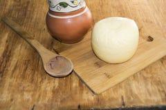 Huvudet av ostgouda skivade stycket av tillbringaren av mjölkar skeden på woode Fotografering för Bildbyråer