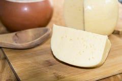 Huvudet av ostgouda skivade stycket av tillbringaren av mjölkar skeden på woode Arkivbild