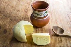 Huvudet av ostgouda skivade stycket av tillbringaren av mjölkar skeden på woode Arkivbilder