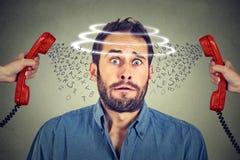 Huvudet rotera Förskräckt man som är stressad och som är nervös från för många ilskna appeller på telefonen royaltyfri fotografi