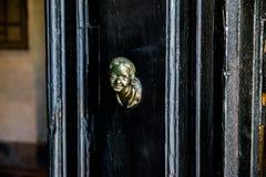 Huvudknackning på en svart dörr royaltyfri bild