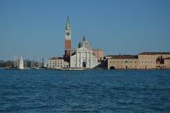 Huvudsaklig fasad av kyrkan av det San Giorgio Maggiore And Its Spectacular Klocka tornet med en Vaporeto som igenom korsar i Ven royaltyfri fotografi