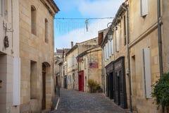Huvudsaklig gata av den medeltida staden av Saint Emilion Vin shoppar kan ses på sidorna Royaltyfri Foto