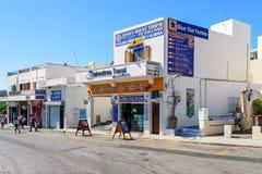 Huvudsaklig gata av den Thira staden med kontoret av loppbyrån fotografering för bildbyråer