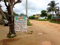 Huvudsaklig gata i Hopkins, Belize, inklusive tecknet för Innies restaurang arkivbild