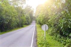 Huvudsaklig gata i tropisk skog för berg med trafiktecknet Arkivbilder