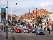 Huvudsaklig gata med gamla byggnader och bilar för röd tegelsten Fotografering för Bildbyråer