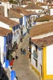 Huvudsaklig gata som flankeras av typiska kalkade hus. Obidos. Portugal Arkivfoto