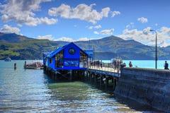 Huvudsaklig hamnplats, Akaroa, Nya Zeeland Passagerare som går för att erbjuda royaltyfri bild
