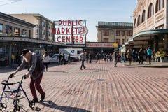 Huvudsaklig ingång till pikmarknaden av Seattle med det egenskaptecknet och folket som kommer och går fotografering för bildbyråer