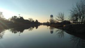 Huvudsaklig kanal i Dos Palos, CA och vattentornet på rätten fotografering för bildbyråer