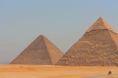 Huvudsaklig sikt av Gizas två största pyramider med Kairostaden i bakgrund Royaltyfri Foto
