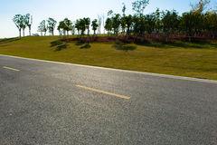 Huvudväg bredvid trän Arkivfoton