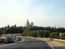 Huvudväg förbi kloster med en hög tempel på en solig dag arkivbild