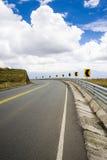 Huvudväg i bergen med en blå himmel Fotografering för Bildbyråer